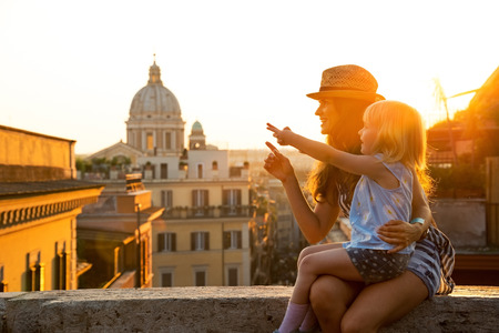 Mother and baby girl sitting on street overlooking rooftops of rome on sunset and pointing Standard-Bild