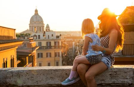 ローマの通りの見下ろす屋根の上を距離に見る夕日に座っている母親と赤ちゃんの女の子 写真素材