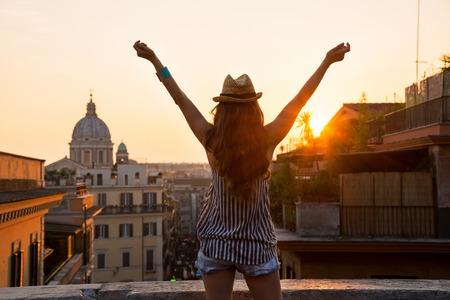 Jonge vrouw die op de daken van Rome op zonsondergang en blijdschap. achteraanzicht