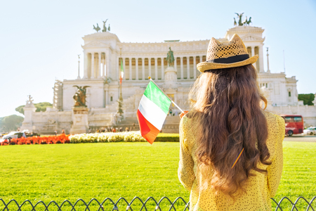 anonym: Young woman with italian flag on piazza venezia in rome, italy. rear view Stock Photo
