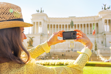 anonym: Closeup on young woman taking photo on piazza venezia in rome, italy. rear view Stock Photo