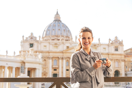 Smiling young woman with photo camera on piazza san pietro in vatican city state Stock Photo