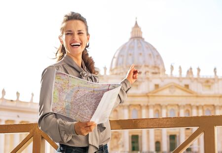 Happy young woman with map pointing on basilica di san pietro in vatican city state photo