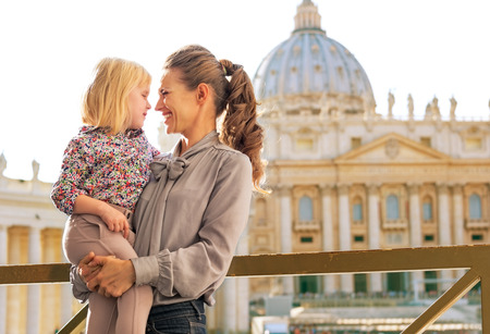 Portrait of happy mother and baby girl on piazza san pietro in vatican city state