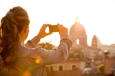 Jonge vrouw nemen foto van rome panorama op zonsondergang. achteraanzicht