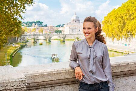 pietro: Portrait of happy young woman on bridge with view on basilica di san pietro