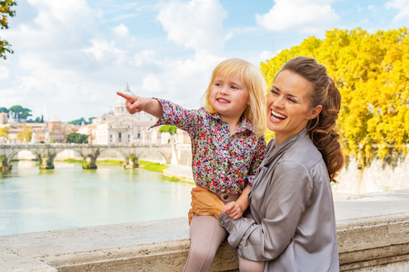 Happy mother and baby girl pointing while on bridge ponte umberto I with view on basilica di san pietro
