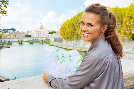Portrait of smiling young woman with map on bridge ponte umberto I with view on basilica di san pietro Stock Photo