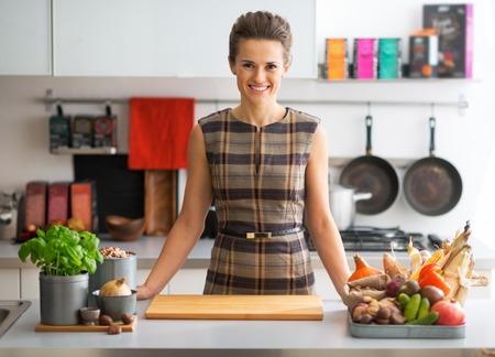 キッチンで野菜と幸せな若い主婦の肖像画