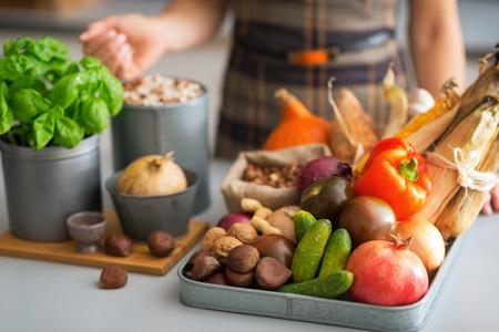 キッチンで野菜を持つ若い主婦にクローズ アップ