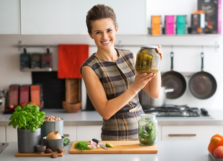 Portrait of happy young housewife showing jar of pickled cucumbers
