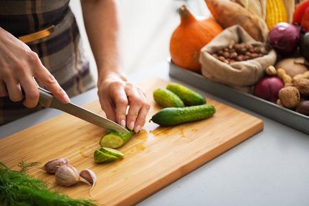 Gros plan sur la jeune femme au foyer couper le concombre de décapage dans la cuisine