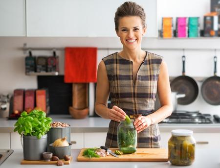 calabacin: Retrato de joven feliz pepinillos ama de casa en la cocina