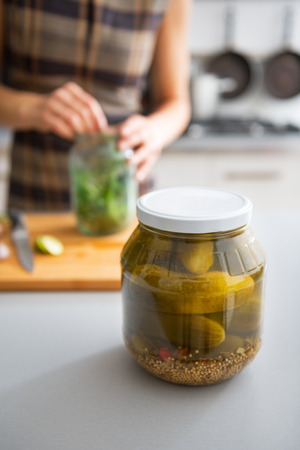 pickling: Closeup on jar of marinated cucumbers on table and housewife pickling in background