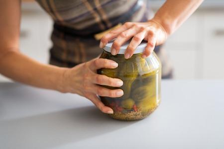 Közeli a fiatal háziasszony nyitó üveg uborka