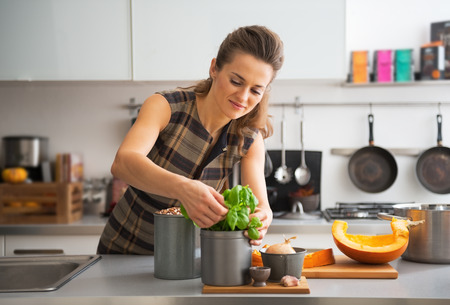 cook house: Happy young housewife using fresh basil while cooking in kitchen