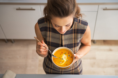 カボチャのスープを食べて若い主婦にクローズ アップ