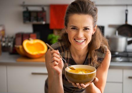 Joven mujer comiendo sopa de calabaza feliz en la cocina