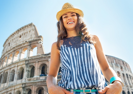 Portrait of happy young woman in front of colosseum in rome, italy
