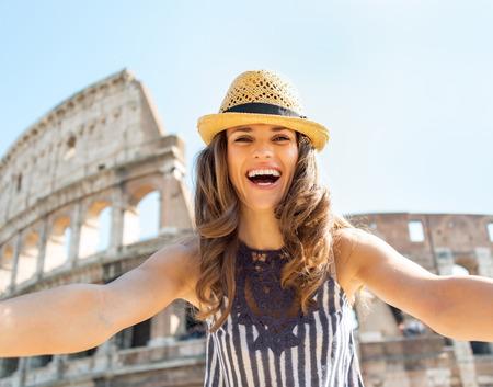 Mujer joven feliz haciendo Autofoto delante del Coliseo en Roma, Italia