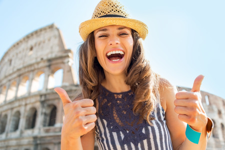 thumbs up gesture: Portrait of happy young woman showing thumbs up in front of colosseum in rome, italy