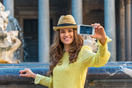 Closeup on young woman making selfie near fountain of the pantheon in rome, italy photo