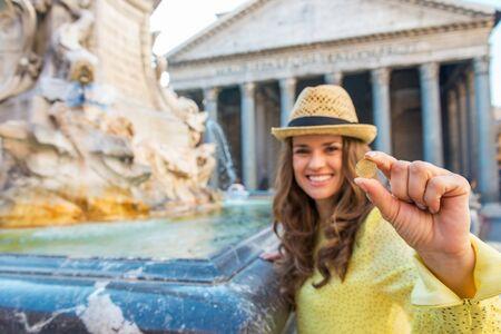 monete antiche: Primo piano sul felice giovane donna che mostra moneta vicino alla fontana del Pantheon a Roma, Italia Archivio Fotografico