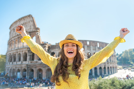 rejoicing: Portrait of happy young woman rejoicing in front of colosseum in rome, italy