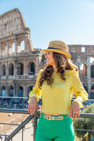 happy old people: Portrait of happy young woman in front of colosseum in rome, italy
