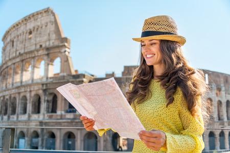 Gelukkige jonge vrouw met kaart in de voorkant van het Colosseum in Rome, Italië