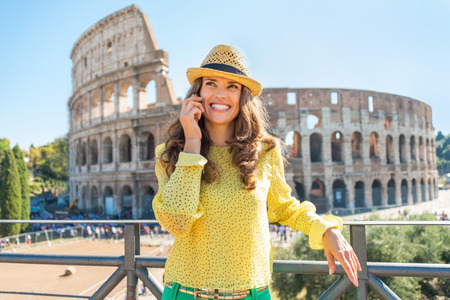 Happy young woman talking cell phone in front of colosseum in rome, italy