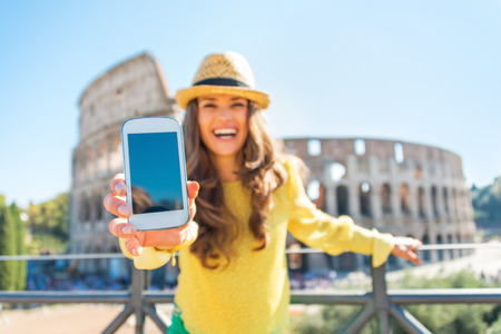 Primer en mujer feliz joven que muestra el teléfono celular en frente del Coliseo en Roma, Italia