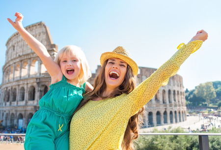 Happy mother and baby girl rejoicing in front of colosseum in rome, italy Stock Photo