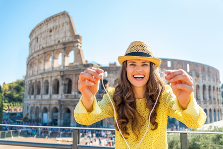 guided: Happy young woman giving headphones with audio guide in front of colosseum in rome, italy