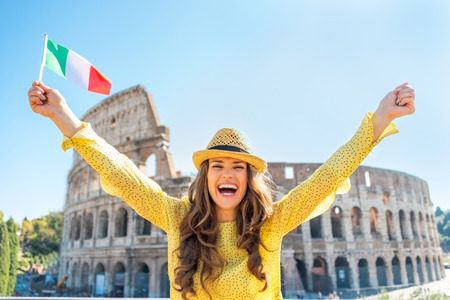 Portrait of happy young woman rejoicing with italian flag in front of colosseum in rome, italy Reklamní fotografie - 36629520