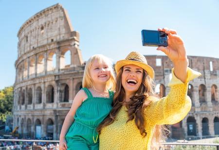 férias: Feliz mãe e bebé fazendo selfie na frente do Coliseu, em Roma, Itália