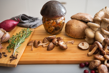 Closeup on jar of pickled mushroom on cutting board photo