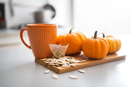 tea bag: Closeup on small pumpkins seeds and tea bag on table