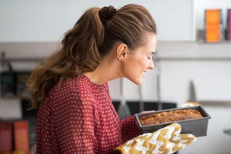 mujer ama de casa: Ama de casa joven que huele fuente de horno con pan
