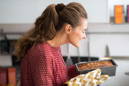 housewife gloves: Young housewife smelling baking dish with bread Stock Photo