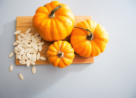 Close-up op kleine pompoenen en zaden op tafel