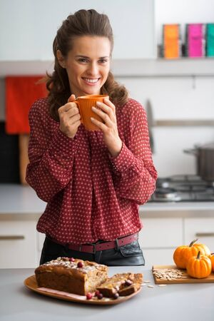 Young housewife drinking tea with freshly baked pumpkin bread with seeds Stock Photo