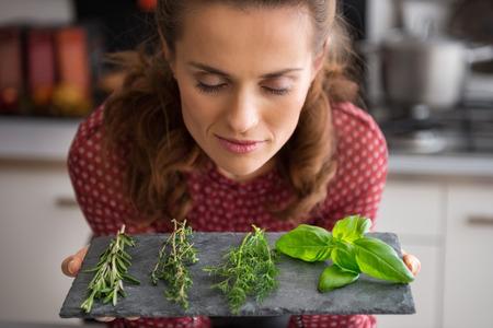 especias: Retrato de joven ama de casa disfrutando de especias frescas hierbas