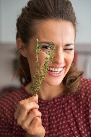 thymus: Portrait of happy young housewife showing fresh thymus