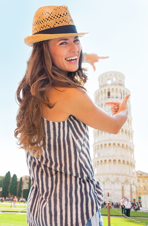 framing: Happy young woman framing leaning tower of pisa, tuscany, italy