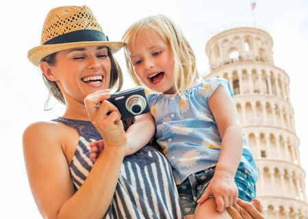 piazza dei miracoli: Portrait of happy mother and baby girl checking photos in camera in front of leaning tower of pisa, tuscany, italy