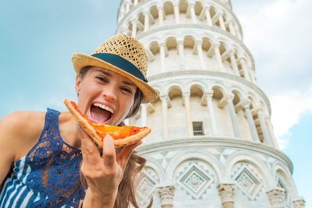 Happy young woman eating pizza in front of leaning tower of pisa, tuscany, italy