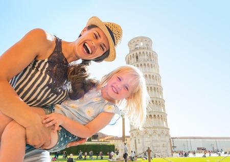 Portret van moeder en baby meisje in de voorkant van de scheve toren van Pisa, Toscane, Italië