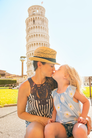 mam: Mother and baby girl kissing in front of leaning tower of pisa, tuscany, italy