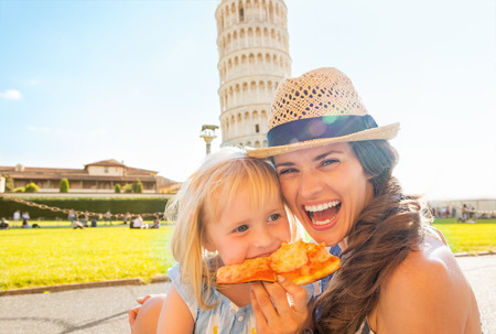 italy street: Portrait of happy mother and baby girl eating pizza in front of leaning tower of pisa, tuscany, italy Stock Photo